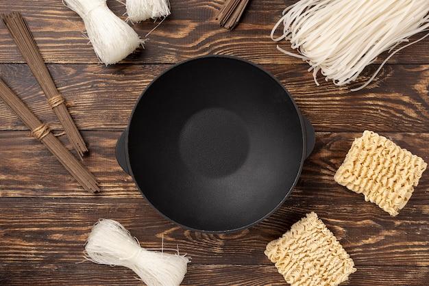 Assortiment non cuit plat de nouilles sur fond en bois avec plaque Photo gratuit