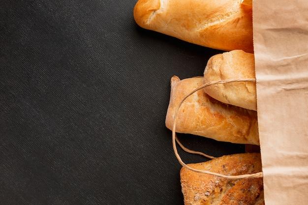 Assortiment de pain dans un sac en papier Photo gratuit
