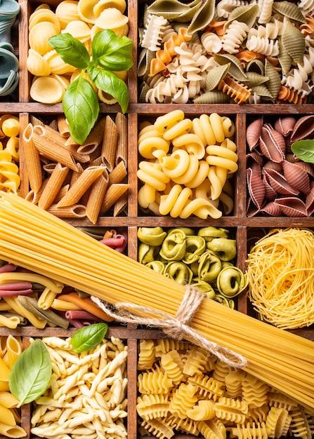Assortiment de pâtes italiennes colorées dans une boîte en bois Photo Premium