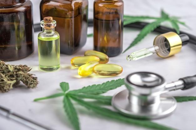 Assortiment de produits à base de cannabis, de pilules et d'huile de cdb sur une feuille d'ordonnance médicale Photo Premium