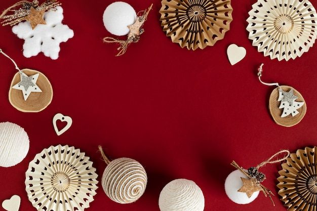 Assortiment De Style Scandinave, Chaleureux Et écologique, Ornements De Noël Faits à La Main Sur Fond Rouge, Mise à Plat, Vue De Dessus Avec Espace Copie Photo Premium