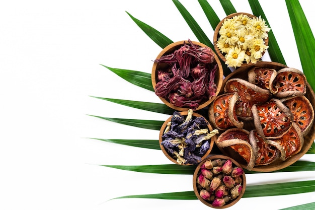 Assortiment de thé tropical sain sain à base de plantes dans des bols en bois isolés sur fond blanc. Photo Premium