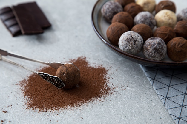 Assortiment de truffes au chocolat avec poudre de cacao, noix de coco et noisettes hachées dans une assiette à dessert Photo Premium