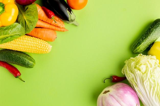 Assortiment vue de dessus de légumes sur fond vert avec espace de copie Photo gratuit