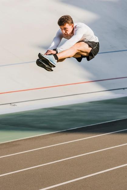 Athlète au milieu d'un saut en longueur Photo gratuit