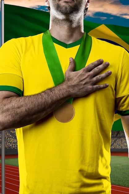 Athlète Brésilien Gagner Une Médaille D'or Devant Un Drapeau Brésilien. Photo Premium