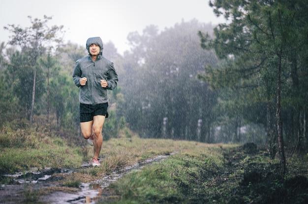 Athlète coureur en sentier forestier veste de sport gris sous la pluie Photo Premium