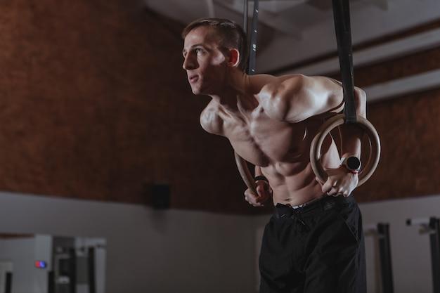Athlète crossfit musclé travaillant sur des anneaux de gymnastique Photo Premium