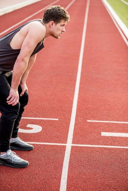 Un athlète épuisé se détendant sur une piste de course Photo gratuit