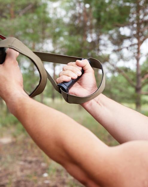 L'athlète fait des exercices de musculation sur les ceintures et le fitness en plein air Photo Premium