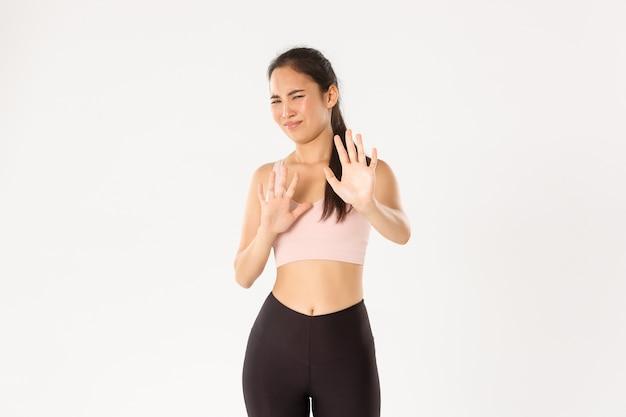 Athlète Féminine Asiatique Réticente Et Mécontente En Tenue De Sport Se Serrant La Main En Signe De Rejet, Grimaçant Et Grimaçant à Cause De Quelque Chose De Dégoûtant. Photo Premium