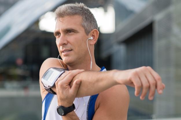 Athlète Masculin D'âge Mûr Qui S'étend Et écoute De La Musique à L'extérieur Photo Premium