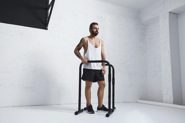 Athlète Masculin Barbu Tatoué Brutal En T-shirt Réservoir Blanc Blanc Debout à Côté De Barres Parallèles Et Barre De Traction à Côté, Prêt à S'entraîner, à La Recherche De Côté Photo gratuit
