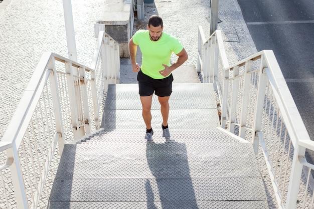 Athlète Masculin Concentré Qui Monte Les Escaliers Photo gratuit