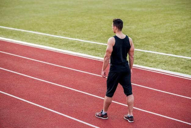 Un athlète masculin debout sur une piste de rack rouge dans le stade Photo gratuit
