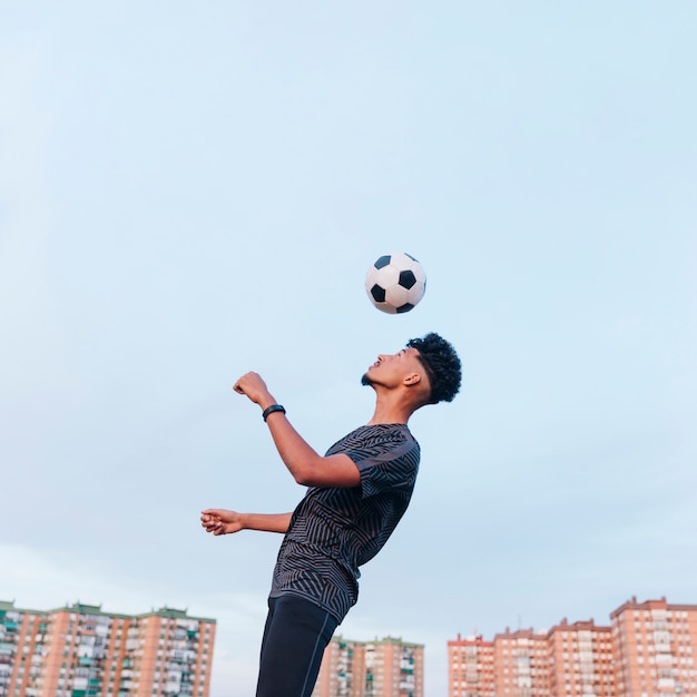 Athlète masculin de formation avec ballon de foot contre ciel bleu Photo gratuit