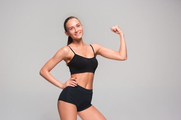 Athlète Musclé Jeune Femme Posant Sur Fond Gris Photo gratuit