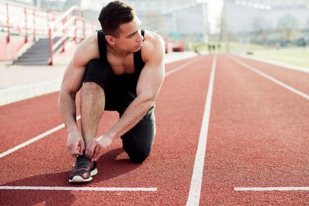 Un athlète sprinter s'apprête à courir pour attacher des lacets sur les pistes de course du stade Photo gratuit