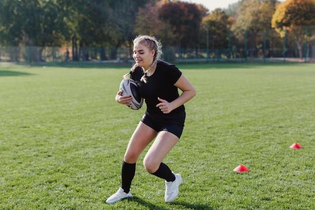Athlétique femme blonde tenant un ballon de foot Photo gratuit