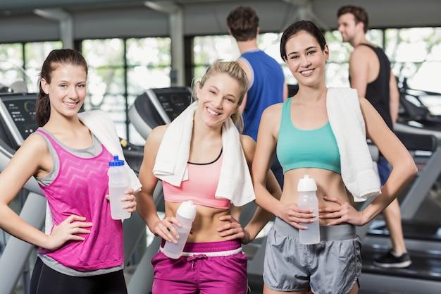 Athlétique femmes souriantes posant avec une bouteille d'eau dans une salle de sport Photo Premium