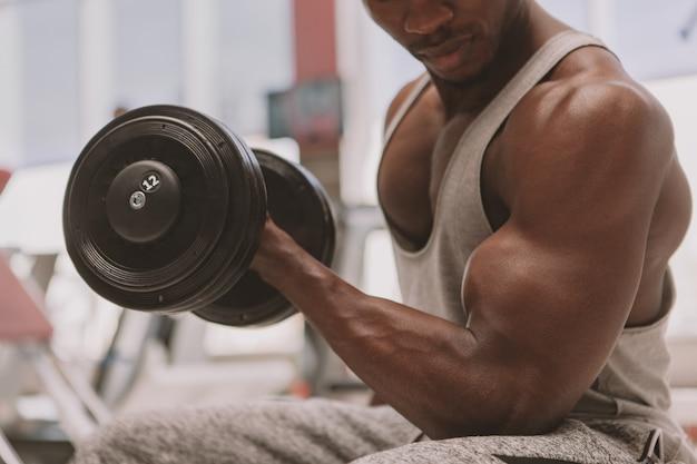 Athlétique homme africain travaillant avec des haltères à la gym Photo Premium