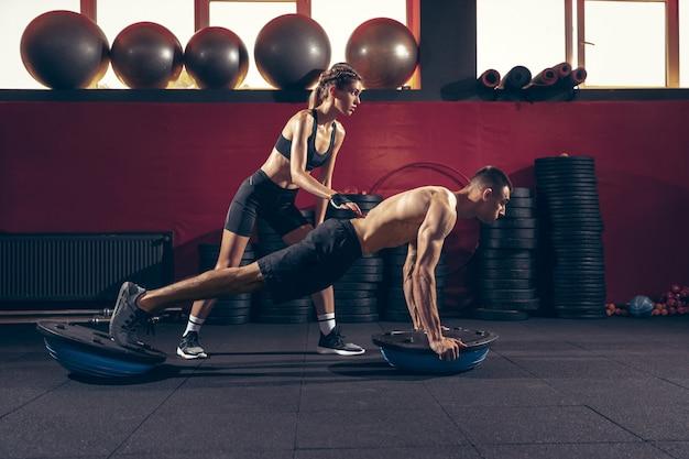 Athlétique Homme Et Femme Avec Une Formation D'haltères Et Pratiquant Dans La Salle De Gym. Photo gratuit