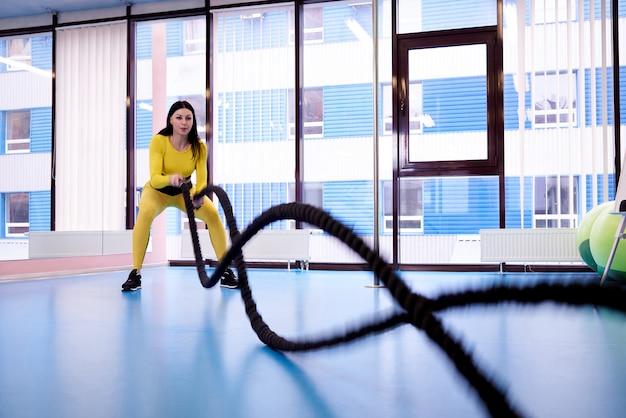 Athlétique jeune femme avec des cordes pour une formation en forme de croix dans la salle de gym. Photo Premium