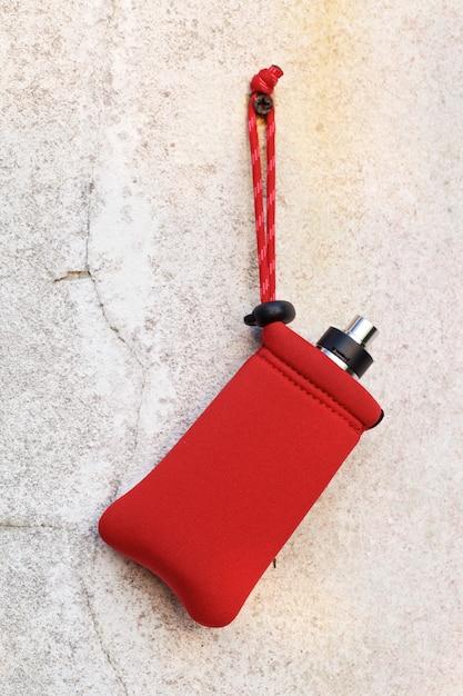 Atomiseur Dégoulinant Reconstructible Haut De Gamme Et Mods De Boîte Dans Un Sac De Poche Rouge Suspendu à Une Vieille Texture De Mur De Béton Blanc, équipement De Vaporisateur, Mise Au Point Sélective Photo Premium