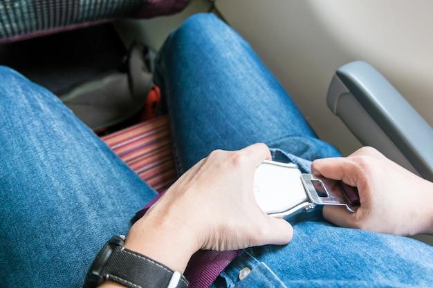 Attachez la ceinture de sécurité à la main sur l'avion avant de décoller Photo Premium