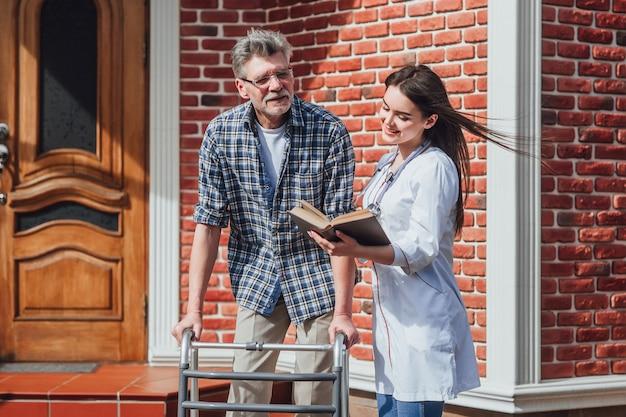 Attente miracle infirmière à l'extérieur en prenant soin d'une femme âgée malade en fauteuil roulant. Photo Premium
