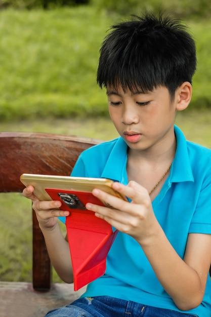 Une attention mignonne de garçon asiatique à jouer à la tablette dans le temps libre Photo Premium