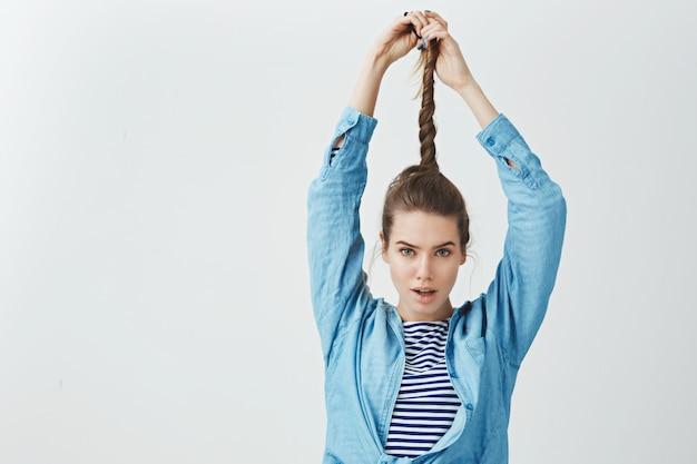 Attractive Ambitieuse Confiante Jeune Femme Tirant Les Cheveux Tordus à La Recherche D'un Appareil Photo Sexy Audacieux, Portant Des Vêtements Amples à La Mode, Résultat Satisfait En Appliquant Un Nouveau Shampooing, Photo gratuit