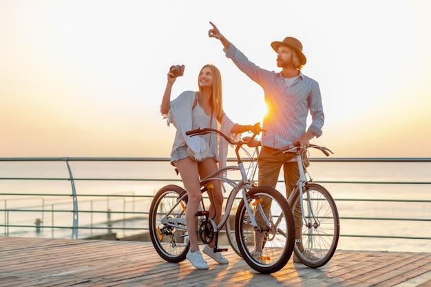 Attractive Couple Heureux Voyageant En été Sur Des Vélos, Homme Et Femme Aux Cheveux Blonds Mode De Style Hipster Boho S'amuser Ensemble, Prendre Des Photos De Tourisme Photo gratuit