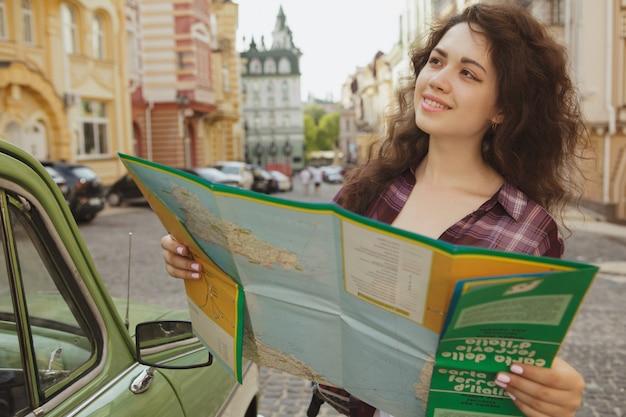 Attractive femme touriste utilisant une carte pour faire du tourisme Photo Premium