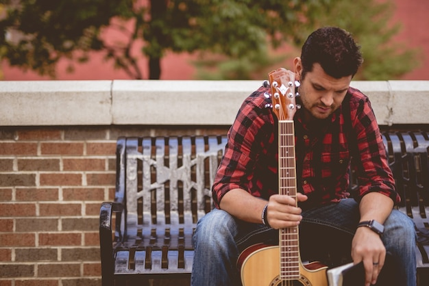 Attractive Homme Blanc Assis Sur Un Banc Tenant La Guitare Photo gratuit