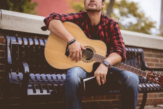 Attractive Homme Blanc Assis Sur Un Banc Tenant La Guitare Photo gratuit