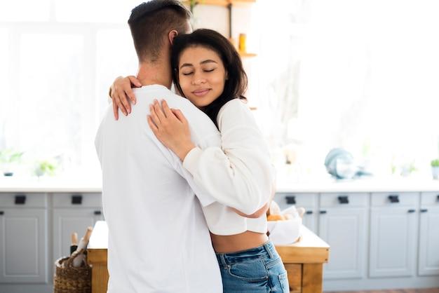 Attractive jeune femme ethnique embrassant son petit ami avec des yeux fermés Photo gratuit