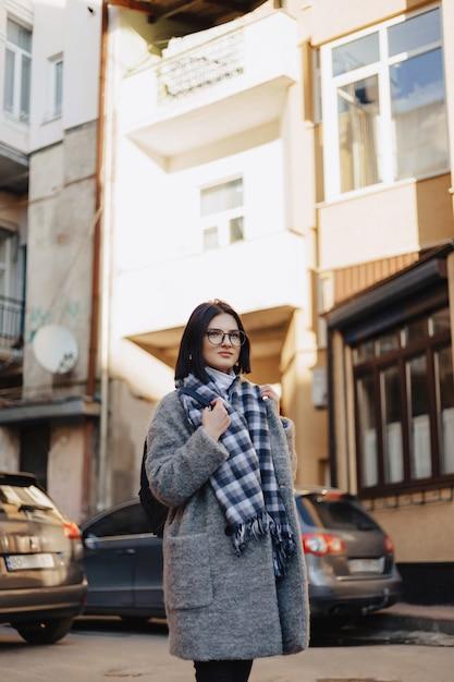 Attractive positive jeune fille portant des lunettes dans un manteau dans la rue Photo Premium
