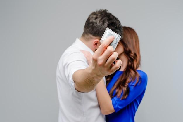 Attrayant couple s'embrasser avec un préservatif en bref isolé sur fond gris Photo Premium