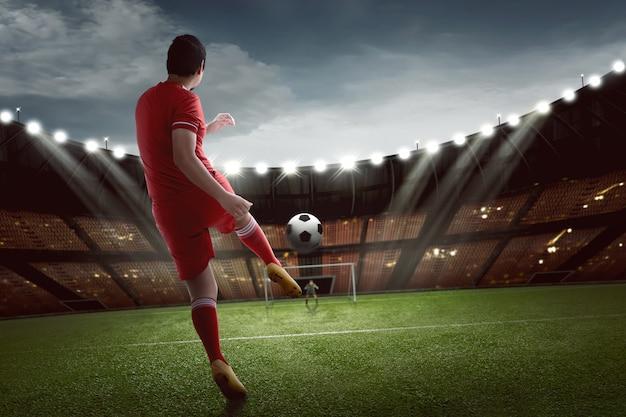 Attrayant footballeur asiatique tirant le ballon au but Photo Premium
