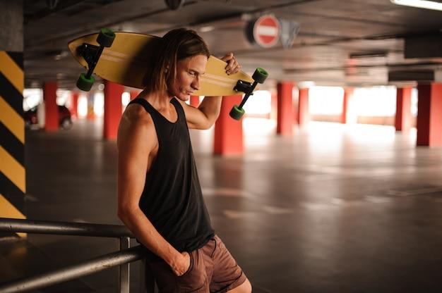 Attrayant gars aux cheveux longs, regardant vers le bas et tenant un longboard Photo Premium