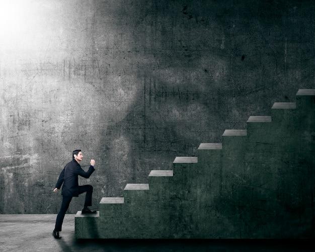 Attrayant homme d'affaires asiatique intensifiant un escalier Photo Premium