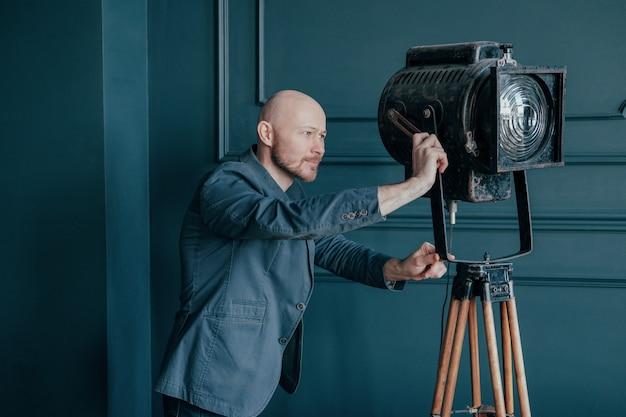 Attrayant homme chauve adulte avec barbe en costume regardant vieux luminaire, vidéo lumière Photo Premium