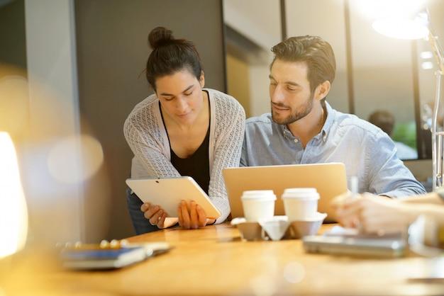 Attrayants collègues partageant des idées d'entreprise dans un espace de travail commun Photo Premium