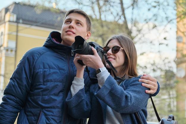 Attrayants touristes masculins et féminins prenant des photos avec appareil photo Photo Premium