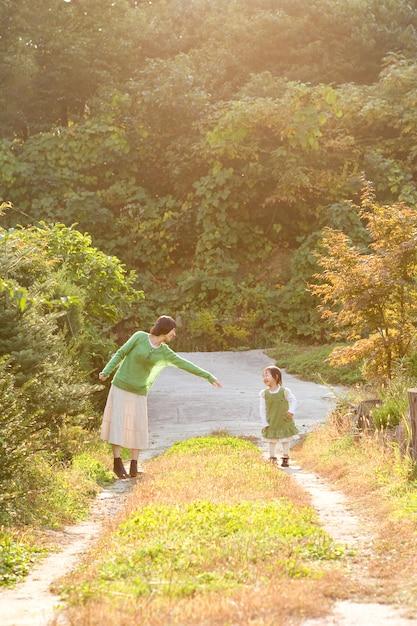 Au coucher du soleil dans le parc, la mère et l'enfant s'amusent. Photo Premium