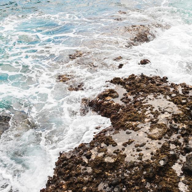 Au-dessus de la mer vue touchant la côte rocheuse Photo gratuit