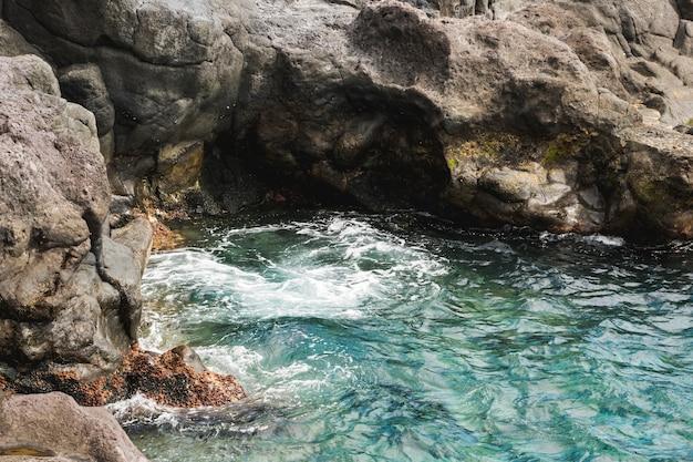 Au-dessus vue gros plan eau ondulée à la côte rocheuse Photo gratuit