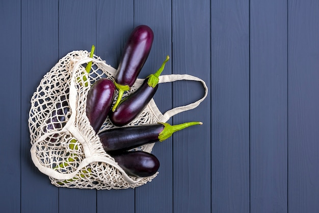 Aubergine dans un sac en maille écologique avec aubergine sur bois gris foncé. Photo Premium