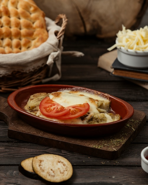 Aubergine grillée garnie de fromage fondu dans un plat en terre cuite Photo gratuit